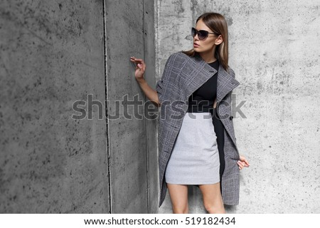 high fashion portrait of young elegant woman outdoor. Grey coat, cat eye sunglasses, grey wall background #519182434
