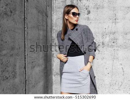 high fashion portrait of young elegant woman outdoor. Grey ��oat, cat eye sunglasses, grey wall background - Shutterstock ID 515302690