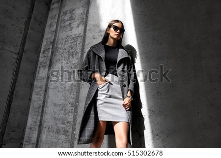 high fashion portrait of young elegant woman outdoor. Grey ��oat, cat eye sunglasses, grey wall background