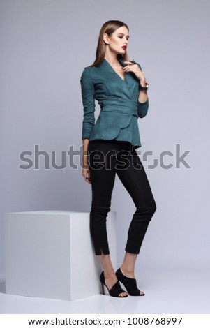 high fashion portrait of young elegant woman. Suede jacket, skinny black pants, black heels shoes #1008768997