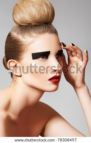 High fashion style. Cosmetics and make-up. Beautiful woman model with perfect clean skin, creative black eye make-up, dark red lips and fashion bun hairstyle. Blond chignon bun on her head