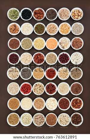 High fiber health food sampler with cereals, nuts, seeds, grain, fruit, herbs and legumes with foods high in omega 3 fatty acid, antioxidants and vitamins, top view. With titles. #763612891