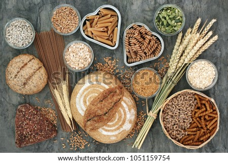 High fibre health food concept with multi seed whole grain bread loaf and seeded rolls, whole wheat pasta, grain, seeds and cereals. Food high in omega 3 fatty acids, antioxidants, protein & vitamins. #1051159754