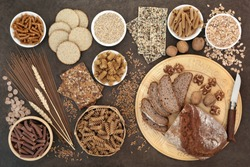 High fibre health food with whole wheat walnut and rye bread, whole grain pasta, oatmeal and seeded crackers, barley oats, bran flakes and wheat sheath on lokta paper background.