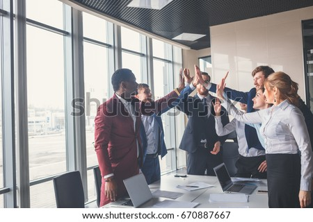 High-five! cheerful young business people giving high-five while their colleagues looking at them and smiling #670887667