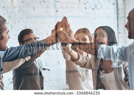 High-five! Group of business colleagues giving each other high-five while working behind the glass wall in the board room #1068846230
