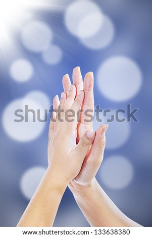 High five hand gestures between mother and son on blur background