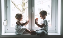 High five! Little children on background of window. Photo of kids leisure at home, childcare, safety symbol, family life. Brother and sister in white clothes on vacation. Girl give five to a boy.