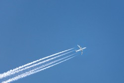 high-flying airplane on the clear blue sky leaving white trace behind, bottom view, copy space/ Aircraft flying overhead left to right leaves four condensation trails/ Vacation, travel, plane concept