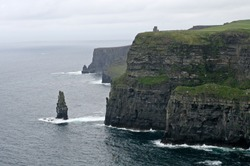High grassy cliffs and the small separate cliff on the sea coast and heavy fog in the summer