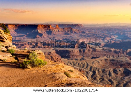 High, hazy view of the rugged desert terain, mountains and canyons at sunset