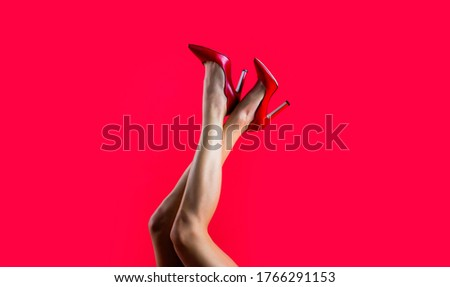 High heel shoes. Beautiful legs woman. Pretty female legs with red high heels on red background. Perfect female legs wearing high heels. Shapely legs, a girl in shoes high-heeled.