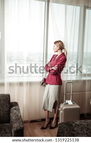 High-heeled shoes. Blonde-haired businesswoman wearing high-heeled shoes standing near window in hotel #1319225138