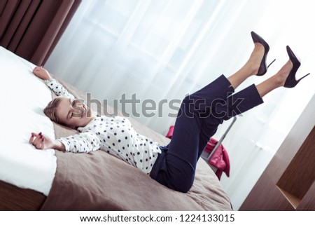 High-heeled shoes. Elegant stylish businesswoman wearing high-heeled shoes lying on bed in hotel #1224133015