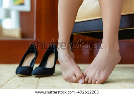 High heels shoe feet pain. Closeup of woman barefoot with painful toes has removed her formal stilettos at work or is embarrassed of foot problem, nails or in discomfort at shoe store or home.