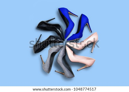 High heels. Top view different colors of high heels isolated blue pastel background. High heels arranged in a circle. Matt and shiny high heels. Fashion and beauty concept. Footwear for women. #1048774517