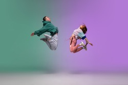High jump. Boy and girl dancing hip-hop in stylish clothes on colorful gradient background at dance hall in neon. Youth culture, movement, style and fashion, action. Fashionable portrait. Street dance