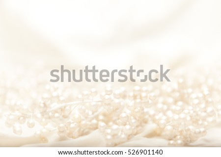 High key image of pearl covered branches on light fabric with shallow depth of field.