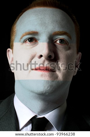 High key portrait of a serious businessman or politician whose face is painted in national colors of argentina flag