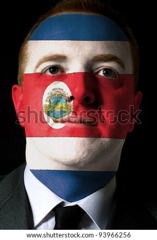 High key portrait of a serious businessman or politician whose face is painted in national colors of costa rica flag