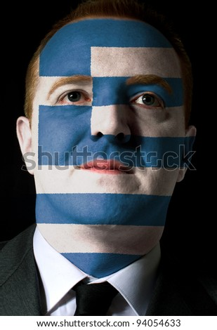High key portrait of a serious businessman or politician whose face is painted in national colors of greece flag