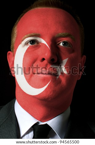 High key portrait of a serious businessman or politician whose face is painted in national colors of turkey flag