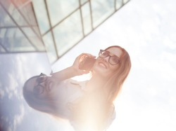 High key portrait of happy businesswoman talking on mobile phone. Young redhead female manager wearing glasses using smartphone at office building