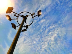 High light pole or electric flood lamp against blue sky in urban city background used for lightening city streets of roads in night.