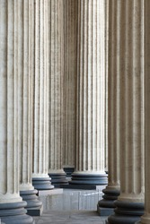 High marble columns as background, architectural design in style of classicism. Architectural pattern of pillars in space. Monochrome ivory white color. Vertical image.