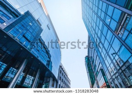 high, modern, futuristic office building exteriors with reflections on the blue glass windows, photographed from the street - angle view #1318283048