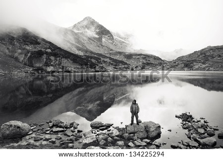 high mountain black and white landscape with hiker and lake
