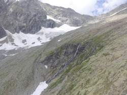 High mountain landscape captured by a drone including a glacier and a waterfall. Shot around The Robert Blanc hut located on the Mont Blanc tour in Savoie in the french alps at 2700 meters of altitude