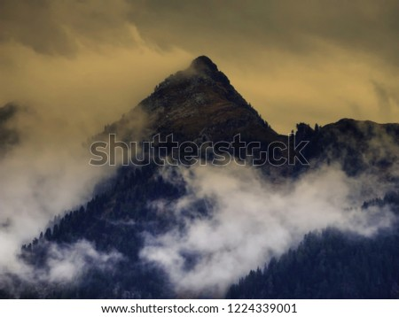 High mountain peak covered by fog and mist,high altitude mountain landscape, steep slope, hill. Frightening atmosphere, bad weather,clouds.Alps,Austria