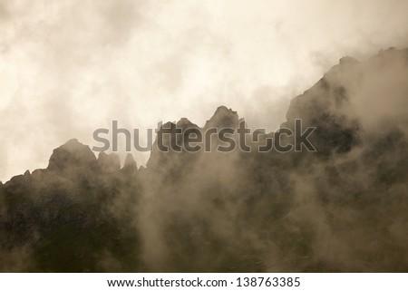 High mountain ridge in thick fog