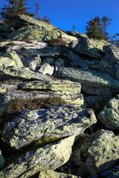 high mountain stone wall depp blue sky at rocky peak trail
