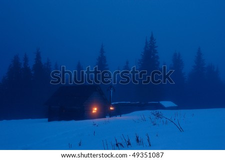 High-mountainous small house in the Ukrainian Carpathians. Winter evening, on a cross with Jesus burns a candle