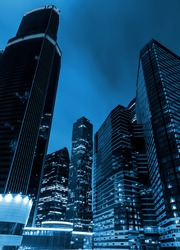 high of the modern business skyscrapers at night, the view from below. Blue tone