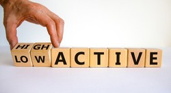 High or low active symbol. Businessman hand turns cubes and changes the word reactive to proactive. Business concept. Beautiful white background, copy space.