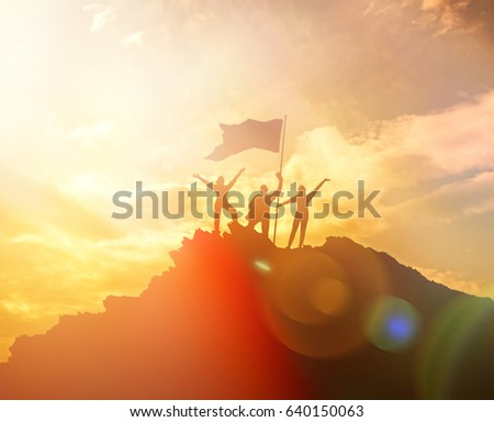 High performance, silhouettes of three people, raise the flag and hands up. A man on top of a mountain. Conceptual design. Against the dramatic sky with clouds at sunset. Success business.