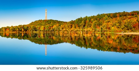 High Point war veterans monument in Kittatinny mountains, New Jersey. High Point is the highest elevation in the NJ state at 1,803 feet (550 m). Colorful fall foliage reflects in Lake Marcia.