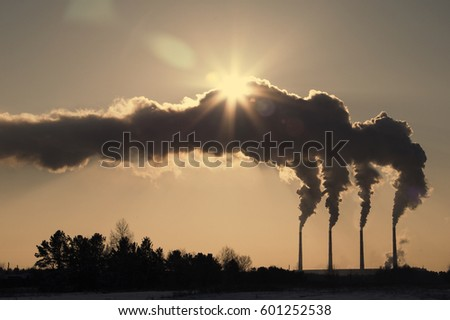 High pollution from coal power plant. Black smoke against sun. Smoking chimney of industrial buildings complex #601252538