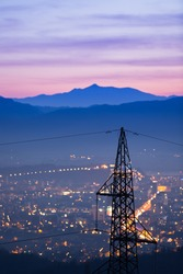 High power electricity poles in urban area. Energy supply, distribution of energy, transmitting energy, energy transmission, high voltage supply concept photo.
