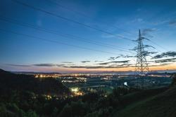 High power electricity pylon above a city skyline
