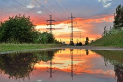 High-power line - power lines and the sunset reflected in the water after the rain