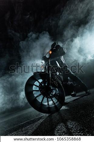 High power motorcycle chopper at night. Smoke effect on dark background. #1065358868