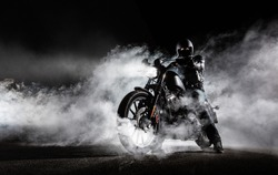 High power motorcycle chopper with man rider at night. Fog with backlights on background.