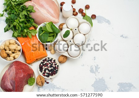 Shutterstock High protein food - fish, meat, poultry, nuts, eggs. Products goof for healthy hair. Space for text