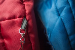 High quality and durable security key loop sewn attached on backpack attachment for keychain or carabiner on red and blue nylon outdoor jacket and backpack duffle bags