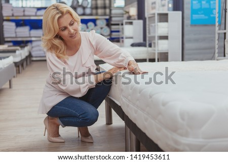 High quality home goods concept. Beautiful elegant mature woman shopping for furniture at department store. Attractive female customer examining orthopedic mattress at furnishings shop