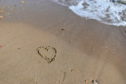 High quality image. Image of a beach with a heart drawn in the sand. Image of love.